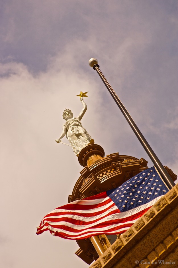 October 8, 2015: The Goddess of Liberty replica atop the Texas Capitol holds her gilded star high against a bank of soft clouds.