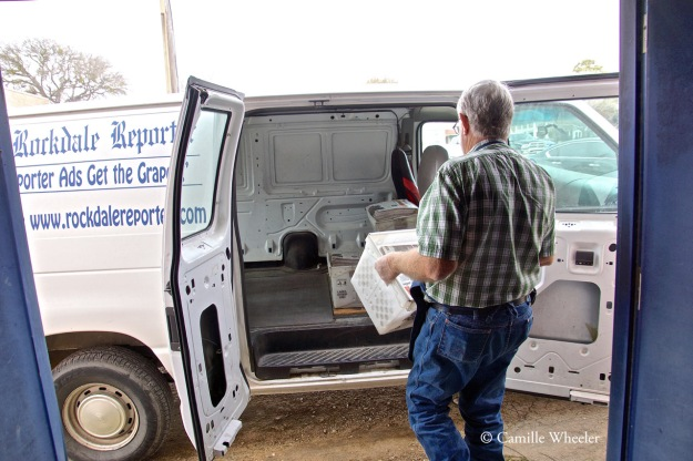 Cliff Dungan, a printer, photographer, and fix-it man for The Rockdale Reporter, carries a tub of just-labeled newspapers to the newspaper's van. Next stop: the post office next door.