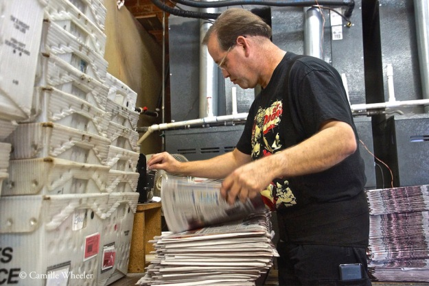 Production Manager Shannon Whorton whips through stacks of soon-to-be-mailed newspapers with the aid of an electric label dispenser.