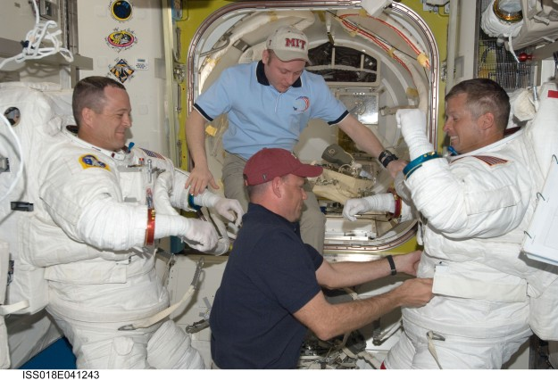 Photo credit: NASA After a March 19, 2009, spacewalk outside the International Space Station, astronauts Ricky Arnold, left, and Steve Swanson shed their Extravehicular Mobility Unit spacesuits with help from Expedition 18 commander Michael Fincke, top center, and Tony Antonelli, STS-119 pilot for the 28th space shuttle mission to the space station.