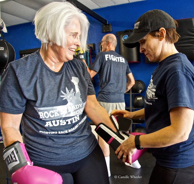 "Coach Kristi Richards completed Rock Steady Boxing coaching certification training in September 2015 as one of the final steps toward her dream job: coach and founder of Rock Steady Boxing Austin, which held its first class on Nov. 4, 2015. Richards scans the gym during classes, watching for the first signs of those who need help. She's quick to offer a steadying hand, help someone glove up between workout stations — Meridith Devine, left, in this instance — or plant herself beside boxers, reminding them of punching sequences: ""Jab, hook, uppercut. Jab, hook, uppercut ..."" Described as ""electric and positive"" by one of her boxers, Richards draws upon the Rock Steady Boxing curriculum and her background as a senior fitness group instructor to offer diverse workouts. ""Just going to a regular gym, sure it's great for them, but it's a whole lot more fun to hit stuff,"" she says of her boxers, all of whom have Parkinson's disease."